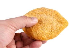 Hand hält Cordon Bleu - paniertes Putenfleisch, gefüllt mit Schinken und Käse, isoliert vor weißem Hintergrund