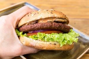 """Hand hält den veganen, fleischlosen Burger """"Naturbursche"""" der Marke Moving Mountains, mit karamellisierten Zwiebeln, Champions und Salat"""