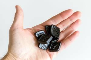 """Hand hält die handlichen, viereckigen """"Oldtimers van Autodrop"""" - Lakritz, eine Süßigkeit aus den Niederlanden"""