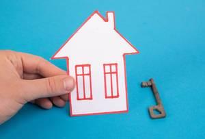 Hand hält ein gebasteltes Haus aus Papier vor blauem Hintergrund, neben einem Vintage-Haustürschlüssel