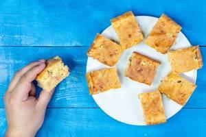 Hand hält ein hausgemachtes Kuchenstück, gefüllt mit Käse und Schinken, auf einem blauen Tisch