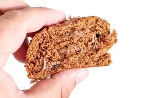 Hand hält ein Stück der Schokoladenkuchenrolle, vor weißem Hintergrund