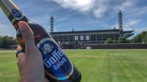 """Hand hält eine Flasche Bier Gaffel Kölsch vor der Stadtwahrzeichen """"RheinEnergie-Stadion"""""""