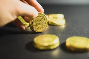 """Hand hält eine mexikanische Schokoladenmünze mit dem Aufdruck """"Zwei Pesos"""""""