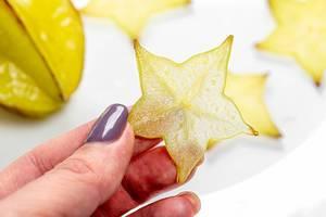 Hand hält eine sternförmige Scheibe der gelben Sternfrucht in der Hand