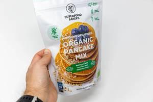 Hand hält eine vegane und biologische Pfannkuchen-Backmischung mit Zimt & Baobab-Pulver von Superfood Bakery, als glutenfreies Essen