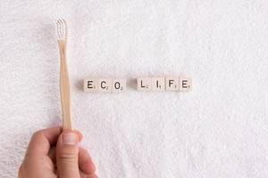 """Hand hält eine Zahnbürste aus Bambus über ein weißes Handtuch, neben den Buchstabensteinen """"Eco Life"""" / Ökologisches Leben"""