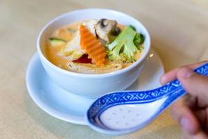 """Hand hält einen asiatischen Reislöffel, vor veganer Vorspeise """"Tom Yum"""", Kokosmilch-Suppe mit gesundem Gemüse & Tofu als Fleischersatz"""