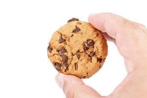 Händ hält einen kreisrunden Keks mit Schokoladenstücken