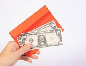Hand hält einen roten Umschlag mit amerikanischen Geldscheinen