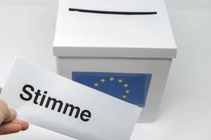 Hand hält einen Stimmzettel für die Europawahl vor einer Wahlurne, zur Abstimmung des Europäischen Parlaments der EU