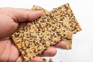 Hand hält gesunde Kräcker mit Leinsamen und Sesam vor weißem Hintergrund