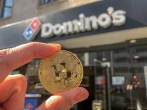 Hand hält goldene Bitcoin-Münze, da man bei Dominos Pizza am Hohenstaufenring in Köln mit der Kryptowährung zahlen kann