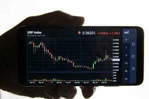 Hand hält Mobiltelefon mit dem Zeitverlauf des XRP Index (Ripple) vor weißem Hintergrund