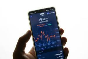 Hand hält Smartphone mit dem Aktienkurs von Tron (TRX) auf dem Bildschirm