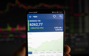 Hand hält Smartphone mit Diagramm des NASDAQ 100 auf dem Display vor dunklem Hintergrund