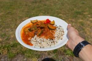 Hand hält veganes Ratatouille aus Zucchini, Tomaten und Zwiebeln mit Wildreis auf dem BarCamp Koblenz