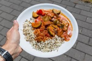 Hand hält vegetarisches Ratatouille mit Wildreis auf weißem Teller auf dem BarCamp in Koblenz