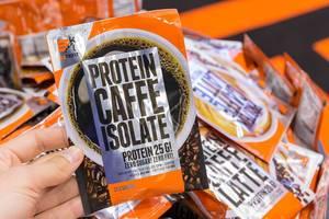 Hand hält Verpackung des isolierten Proteinkaffees von Ex Trifit ohne Zucker und Fett auf der Fibo in Köln