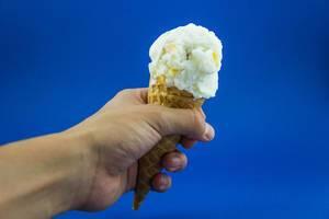 Hand hält Waffel mit Eiscreme vor blauer Wand
