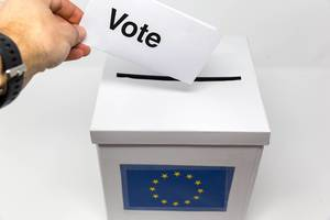 Hand holding a ballot to vote for the European Parliament elections in front of a white ballot box