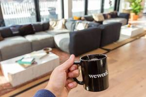 Hand holding a black WeWork cup in front of the joint lounge area of the private office spaces for rent in Cologne, Germany