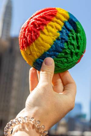Hand holding a rainbow cookie in red, yellow, blue and green, against the background of the Chicago skyscrapers
