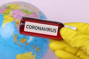 Hand holding blood sample in test tube with Coronavirus text and globe in the background