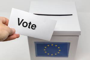"Hand holds a ballot paper with the text ""Vote"" in front of a white box with a European flag on it, as ballot box"
