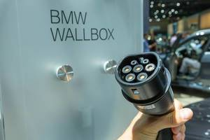 Hand holds a portable BMW i3 type-2 charger in front of BMW Wallbox