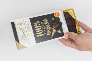 Hand holds an open package of chocolate with 100% cacao by Lindt Excellence with white background