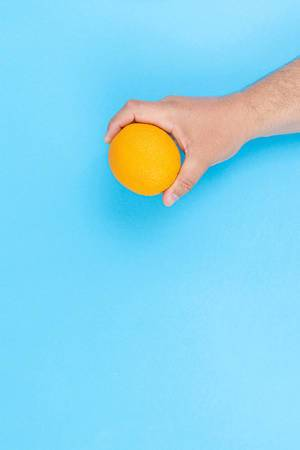 Hand holds Orange fruit above blue background