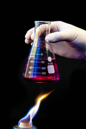 Hand in glove holds flask with chemical solution over fire on black background. (Flip 2020)