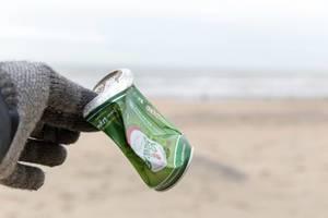 Hand in Handschuh hebt achtlos weggeworfene Bierdose vom Sandstrand auf