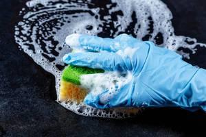 Hand in Latexhandschuh mit Schwamm und Reinigungsmittel