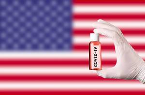 Hand in protective gloves holding COVID-19 test tube in front of flag of USA