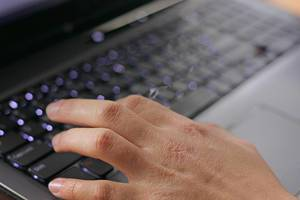 Hand is typing on a black keyboard of a notebook