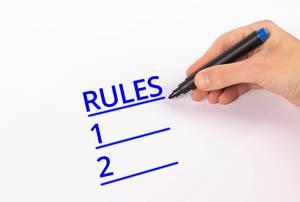 Hand mit blauem Edding-Marker schreibt eine Liste mit Regeln auf