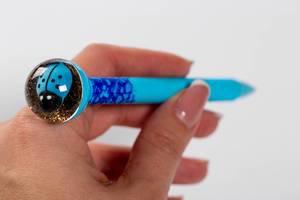 Hand mit blauem Stift auf weißem Hintergrund