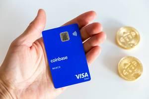 Hand mit Coinbase-Karte neben Bitcoins, mit Kryptowährungen weltweit bezahlen