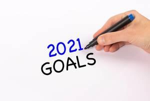 """Hand mit Edding-Marker schreibt """"2021 goals"""" (Ziele für 2021)-Text"""