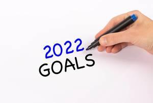 """Hand mit Edding-Marker schreibt """"2022 goals"""" (Ziele für 2022)-Text"""