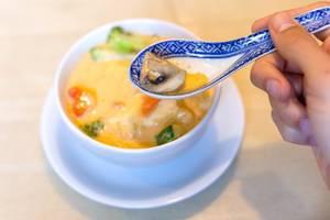 """Hand mit einem asiatischen Porzellan-Löffel vor dem veganen Gericht """"Tom Yum"""" Kokosmilchsuppe, mit Champions, Möhren, Zucchini und Brokkoli"""