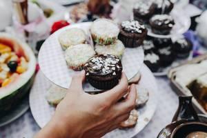 Hand nimmt ein Schoko-Cupcake. Tisch mit Nachspeisen im Hintergrund