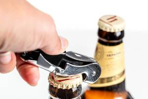 Hand opens a bottle of beer, close up