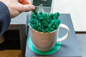 Hand picks one stick from a white mug full of green Starbucks coffee stirrers