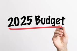 Hand schreibt Budget für 2025 auf ein Whiteboard