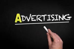 """Hand schreibt das Wort """"Advertising"""" - Werbung - auf eine schwarze Tafel"""