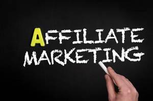 """Hand schreibt das Wort """"Affiliate Marketing"""" mit Kreide auf eine schwarze Tafel"""