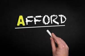 """Hand schreibt das Wort """"Afford"""" - sich etwas leisten können - mit Kreide  auf eine schwarze Tafel"""